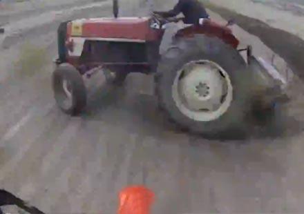 Фермер с трактор сече пътя на моторист